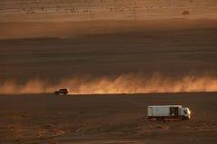 Merzouga, Marokko - 4. Dezember 2018: Camion autocaravana, y-coche levantando polvo Al atardecer en-EL-desierto lizenzfreie stockfotos