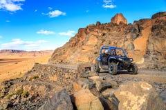 Merzouga Maroko, Feb, - 21, 2016: błękitny Polaris RZR 800 krzyżuje halną drogę w marokańczyk pustyni blisko Merzouga Merzouga je Obraz Royalty Free