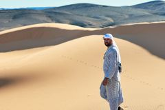 Merzouga Maroko, Grudzień, - 05, 2018: joven berebere caminando pora el desierto mirando cà ¡ Mara obraz royalty free