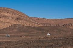 Merzouga, Marrocos - 5 de dezembro de 2018: dois carros 4x4 no meio do deserto árido imagem de stock