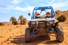 Merzouga, Marrocos - 26 de fevereiro de 2016: a vista dianteira no Polaris azul RZR 800 com ela é pilotos no deserto de Marrocos  imagens de stock royalty free