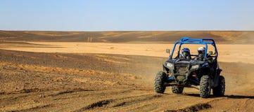 Merzouga, Marrocos - 25 de fevereiro de 2016: A vista panorâmica do Polaris azul RZR 800 e os pilotos em Marrocos abandonam perto fotos de stock royalty free