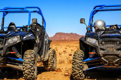 Merzouga, Morocco - Feb 21, 2016: blue Polaris RZR 800 aligned a. Nd stationed with no pilot in Morocco desert near Merzouga. There is a great mountain in the Stock Image