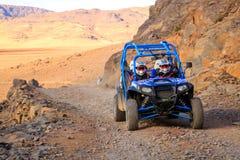 Merzouga, Morocco - Feb 21, 2016: Blue Polaris RZR 800 and pilots crossing on a mountain road in Morocco desert near Merzouga. Mer Stock Photography