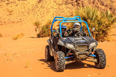 Merzouga, Morocco - Feb 26, 2016: front view on blue Polaris RZR 800 with it's pilots in Morocco desert near Merzouga. Merzouga is Royalty Free Stock Photography