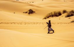 Man walking alone in desert. Merzouga, Morocco - February 25, 2016: Old man in traditional clothes walking alone in the moroccan desert near Merzouga. He walks Stock Image