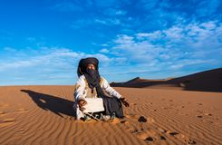 Merzouga, Morocco - October 16, 2018: Tuareg man meditating in the Erg Chebbi sand dunes in the Sahara Desert. Of Morocco stock images