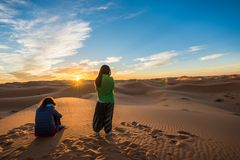 Merzouga, Morocco - October 16, 2018: Two women watching a beautiful sunrise over Erg Chebbi sand dunes near Merzouga, Morocco royalty free stock image