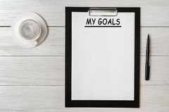 Mes buts énumèrent sur le papier de bloc-notes avec le stylo et le café sur la table en bois image libre de droits