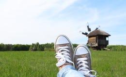 Mes chaussures en caoutchouc kaki avec l'herbe et le vieux moulin dans la campagne Photos stock