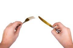 Mes en vork in handen stock afbeelding