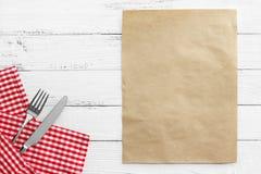 Mes en vork met rood tafelkleed op witte lijst Royalty-vrije Stock Afbeelding