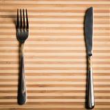 Mes en vork op een houten raad wordt geplaatst die Spatie voor een restaurantmensen Stock Foto