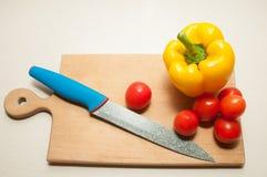 Mes, kersentomaat en groene paprika op scherpe raad Royalty-vrije Stock Afbeelding