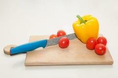 Mes, kersentomaat en groene paprika op scherpe raad Royalty-vrije Stock Fotografie