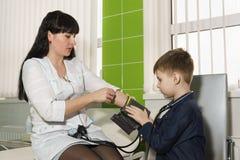Mes mamans une infirmi?re enseigne le fils ? mesurer la pression Connaissance avec ma profession de m?res photographie stock libre de droits
