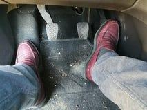 Mes pieds conduisant la voiture image stock