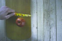 Mes ter beschikking met een appel op een houten achtergrond Stock Fotografie