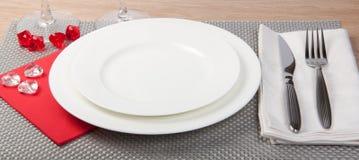 Mes, witte plaat en vork op zilveren achtergrond Stock Fotografie