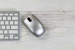 Mesa blanca con el ratón inalámbrico de plata y el teclado parcial Fotografía de archivo libre de regalías
