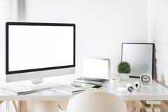 Mesa blanca del diseñador con el ordenador y el ordenador portátil Fotografía de archivo libre de regalías