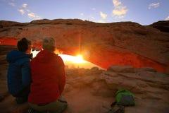 观看日出在Mesa曲拱, Canyonlands国民同水准的游人 免版税图库摄影