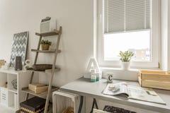 Mesa cinzenta e prateleira de madeira na sala de visitas imagem de stock