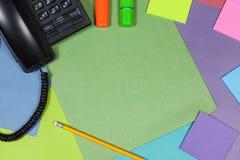 Mesa colorida con las plumas de un teléfono y del highlighter Fotografía de archivo libre de regalías
