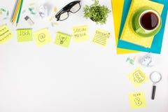 A mesa com fontes do verde, almofada da tabela do escritório de nota vazia, copo, pena, vidros, amarrotou o papel, lupa, flor sob imagens de stock royalty free