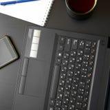Mesa com portátil, o telefone esperto, os cadernos, as penas, os monóculos e um copo do chá Opinião de ângulo lateral fotos de stock