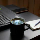 Mesa com portátil, o telefone esperto, os cadernos, as penas, os monóculos e um copo do chá Opinião de ângulo lateral fotos de stock royalty free