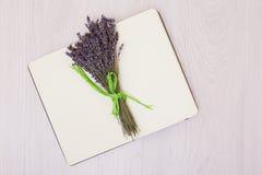 Mesa com zombaria da opinião superior da alfazema das flores acima Abra o bloco de desenho Caderno fotografia de stock royalty free