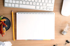 Mesa con el papel, los efectos de escritorio, el ordenador, la libreta en blanco y la bombilla, visión superior Fotos de archivo libres de regalías