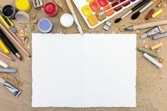 Mesa con la hoja del papel en blanco y las diversas herramientas de dibujo Imagenes de archivo