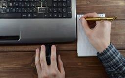 Mesa con la opinión superior del ordenador portátil y de las manos fotos de archivo