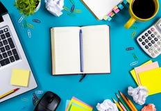 A mesa da tabela do escritório com grupo de fontes coloridas, almofada de nota vazia branca, copo, pena, PC, amarrotou o papel, f Fotos de Stock Royalty Free
