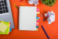 A mesa da tabela do escritório com grupo de fontes coloridas, almofada de nota vazia branca, copo, pena, PC, amarrotou o papel, f fotos de stock