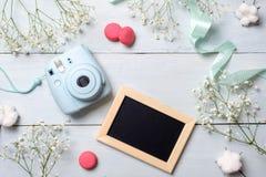 A mesa das mulheres com câmera da foto, moldura para retrato, cookies Quadro mínimo das flores da mola, cores pastel, estilo colo fotografia de stock