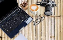 Mesa de bambú con el cuaderno y la cámara imagen de archivo libre de regalías