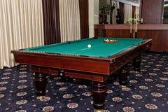 Mesa de billar gastada con una señal y bolas en el gran pasillo del gu Imagen de archivo libre de regalías