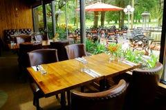 Mesa de comedor acogedora con la opinión del patio Imagenes de archivo