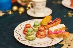 Mesa de comedor adornada de la Navidad con los eclairs deliciosos Imagenes de archivo