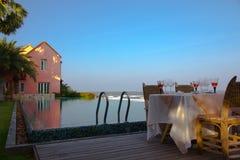 Mesa de comedor al aire libre al lado de la piscina Imagen de archivo