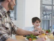 Mesa de comedor de Having Meal At del muchacho y del padre Fotografía de archivo