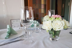 Mesa de comedor de la decoración con el vino de la flor y del vidrio Foto de archivo
