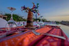 Mesa de comedor romántica en el sol tropical por la piscina, Zanzíbar Imagen de archivo