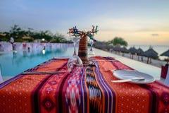Mesa de comedor romántica en el sol tropical por la piscina, Zanzíbar Imagenes de archivo