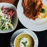 mesa de comedor: una placa de la sopa, del risotto con la chuleta y de la ensalada vegetal foto de archivo