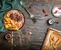 A mesa de cozinha rústica serviu com faixa da carne de porco com uma crosta e cozeu a batata na placa com forquilha, vista superi Imagens de Stock