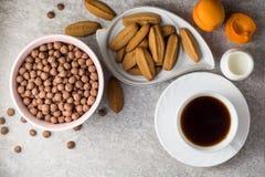 Mesa de desayuno con café, galletas del jengibre, las bolas del cereal del chocolate, la leche, y los albaricoques en el fondo de Fotografía de archivo libre de regalías